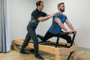 Physiotherapist and patient using pilates reformer.